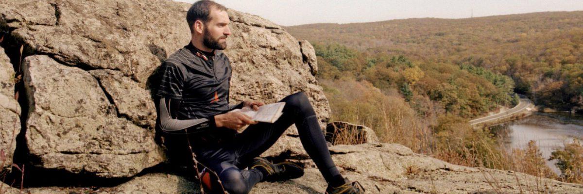 Thierry GUEORGIOU lit une carte assis sur un rocher